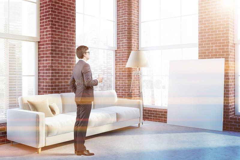 Sofá e lâmpada brancos na sala de visitas do tijolo, homem fotografia de stock