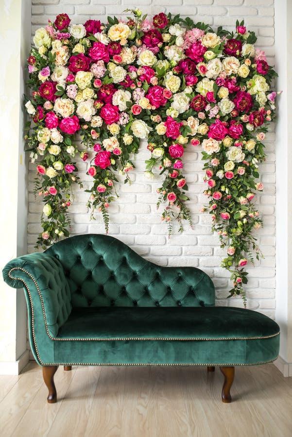Sofá elegante verde na frente da parede das flores fotografia de stock