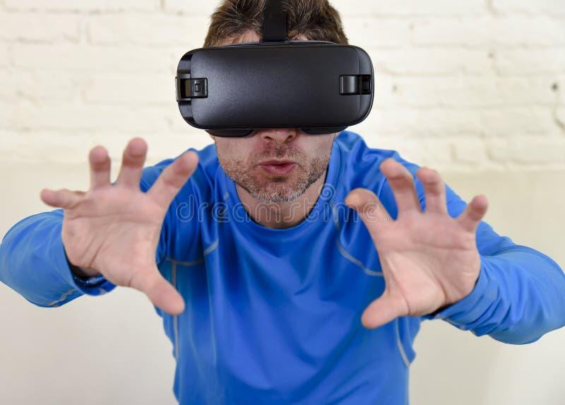 Sofá feliz del sofá de la sala de estar del hombre en casa emocionado usando las gafas 3d que miran la realidad virtual 360 imagenes de archivo