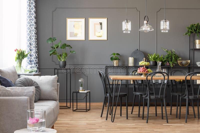 Sofá gris cerca de sillas negras en la tabla debajo de las lámparas en el espacio abierto i imagen de archivo