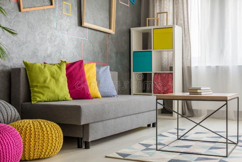 Sofá gris con el amortiguador coloreado imagen de archivo libre de regalías