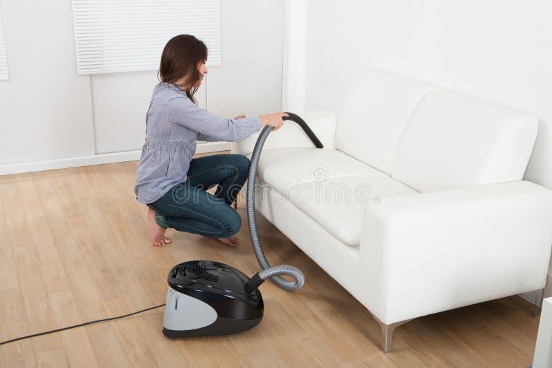 Sofá limpando da jovem mulher em casa fotografia de stock
