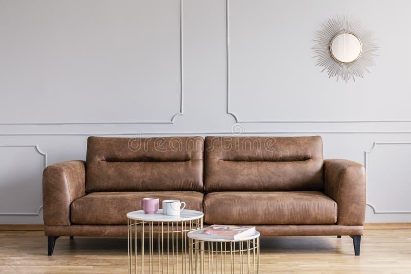Sofá, mesas de centro y espejo de cuero en un interior de la sala de estar fotos de archivo libres de regalías