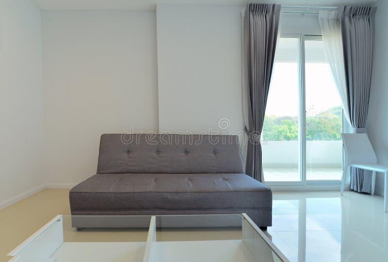 Sofá moderno en la sala de estar blanca con la ventana, diseño interior fotografía de archivo