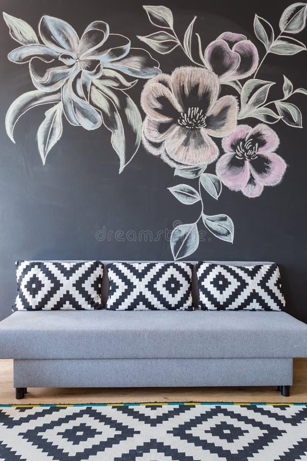 Sofá na parede do quadro-negro foto de stock