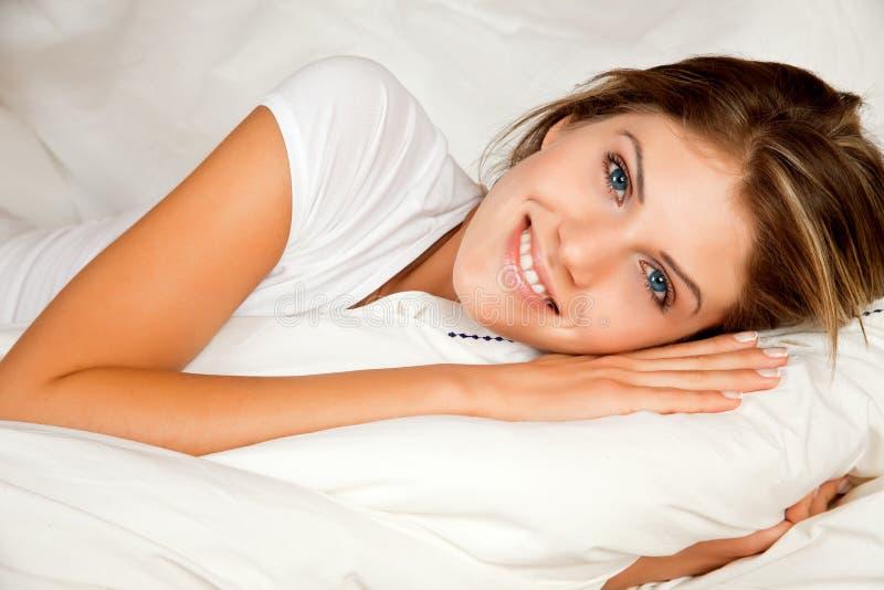 Sofá novo da mulher da beleza na cama fotos de stock