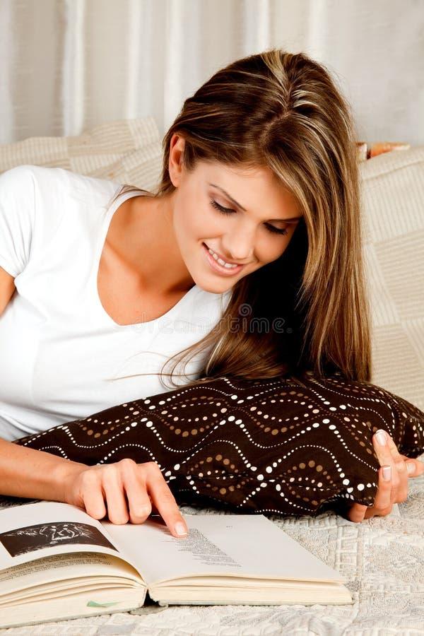 Sofá novo da mulher da beleza na cama e na leitura imagem de stock