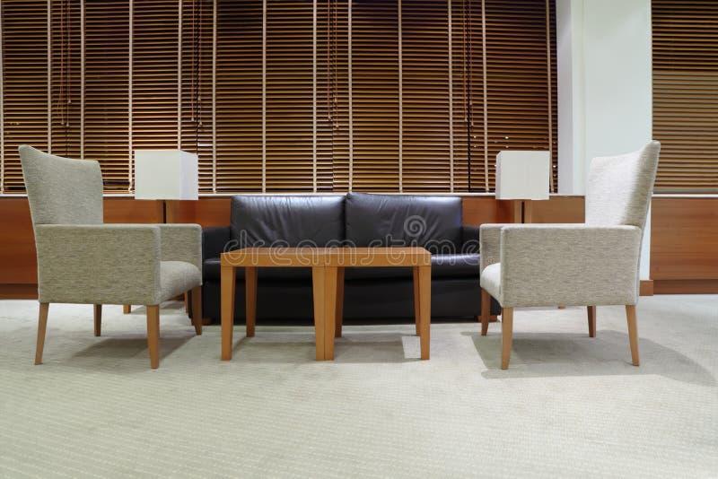 Sofá, poltronas e tabela no escritório foto de stock