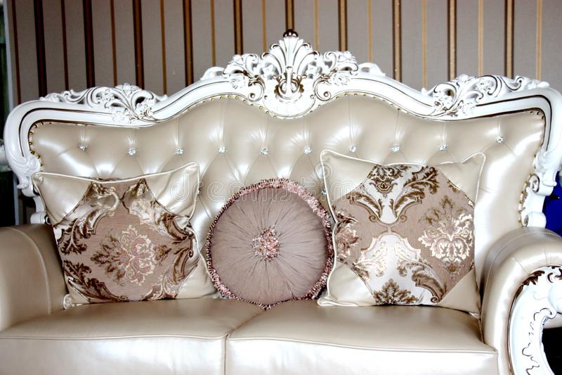 Sofá real con las almohadas en interior lujoso beige imagenes de archivo