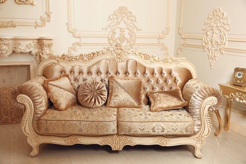 Sofá real con las almohadas en interior lujoso beige con ornamen fotos de archivo