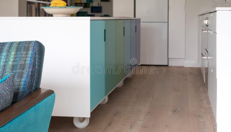 Sofá retro del salón del estilo con la isla de cocina colorida en fondo foto de archivo