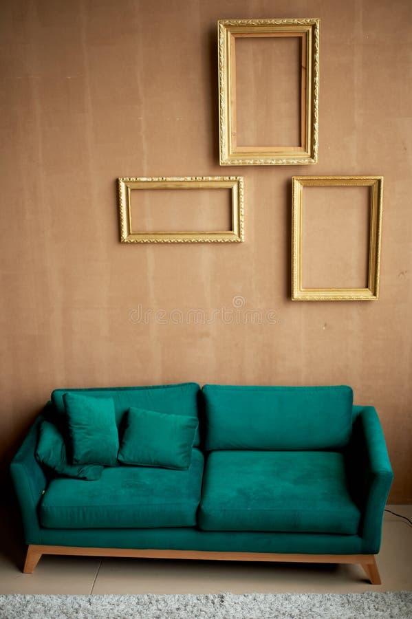Sofá retro del terciopelo esmeralda contra una pared marrón caliente El interior de un cuarto elegante Marcos vacíos del oro en l imagenes de archivo