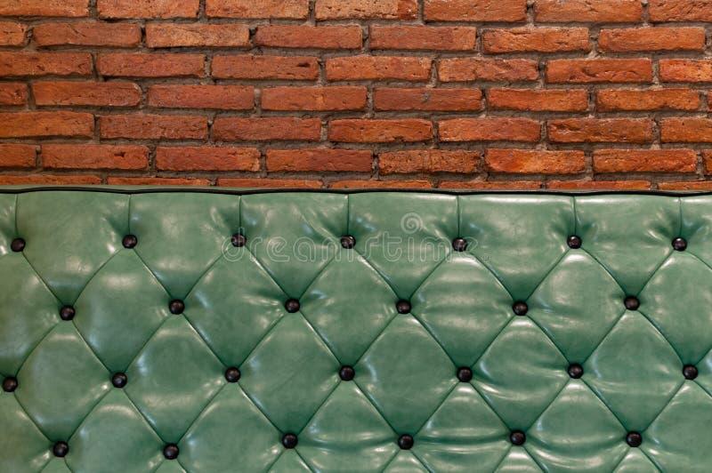 Sofá retro verde em uma sala de visitas com parede de tijolos atrás fotografia de stock