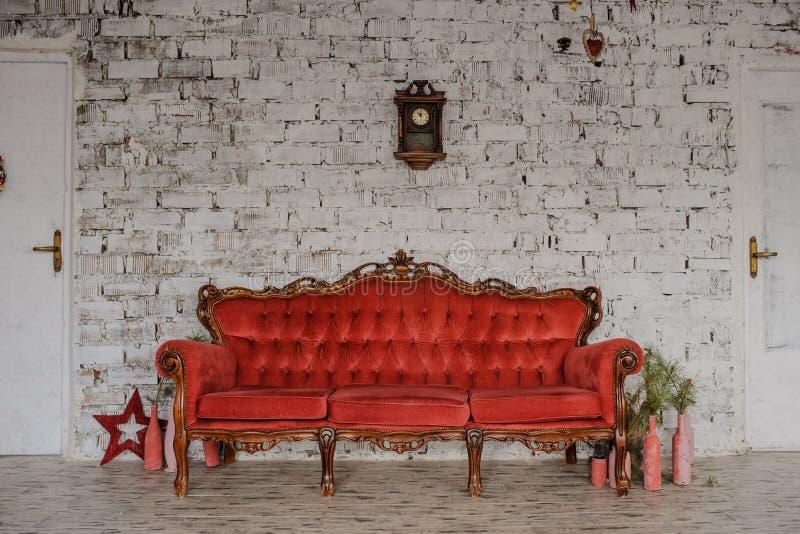 Sofá rojo real del vintage en un cuarto imágenes de archivo libres de regalías