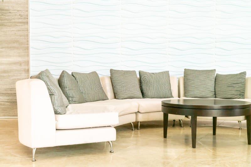 sofá vacío con la almohada en pasillo del hotel imagenes de archivo