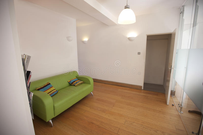 Sofá verde en oficina vacía fotos de archivo
