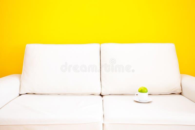 Sofá y taza blancos con la mandarina fotos de archivo libres de regalías