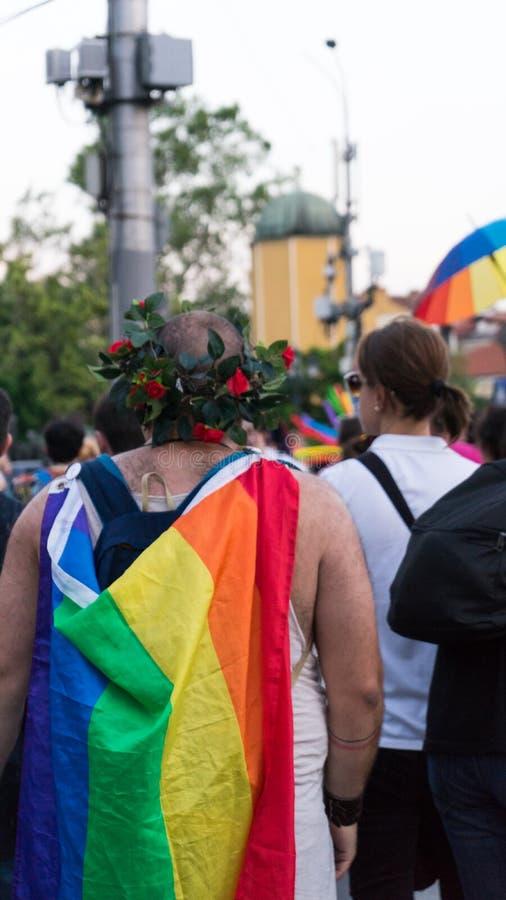 Sofía/Bulgaria - 10 de junio de 2019: Individuo gordo con la bandera del arco iris en la parte posterior y la corona de las flore imagenes de archivo