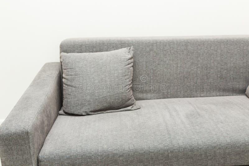 Sof? gris moderno cl?sico con las almohadas en el interior brillante del apartamento Cierre para arriba fotos de archivo libres de regalías