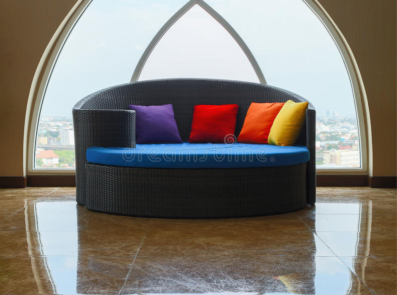 Sofa bed and skylight windows. Huge blue round sofa bed with colorful pillows in front of dome skylight windows stock photos