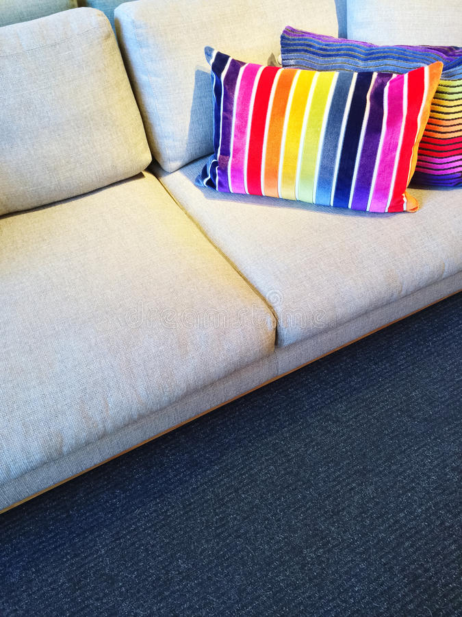 Sofa with bright rainbow striped cushions. Comfortable sofa with bright rainbow color striped cushions stock images