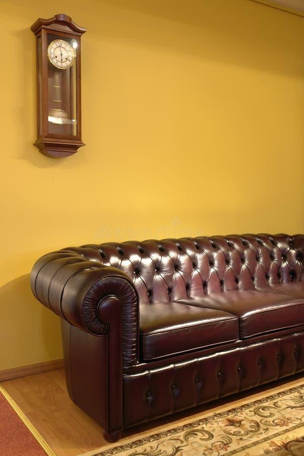 sofa brun de cuir d'horloge photographie stock libre de droits