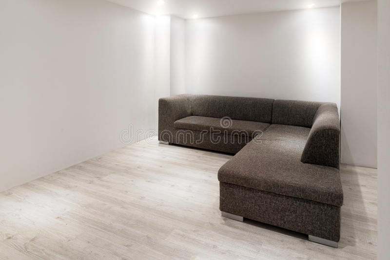 Sofa with chaiselongue in empty renovated apartment stock image