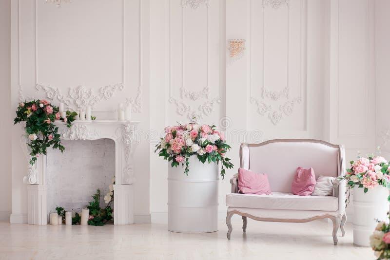 Sofa classique de style de textile blanc dans l'intérieur de vintage avec la cheminée Fleurit les barils peints par ob images libres de droits