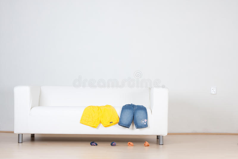 Sofa with clothes and shoes. A white sofa with shorts and shoes royalty free stock image