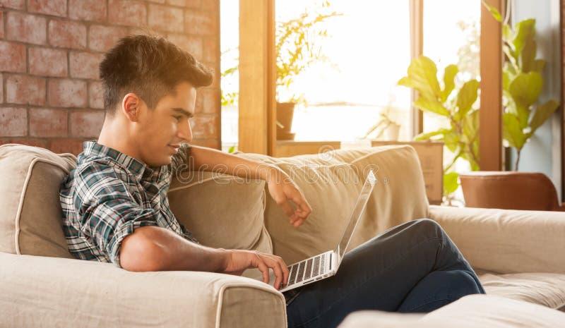 Sofa d'Using Laptop On d'homme d'affaires photo stock