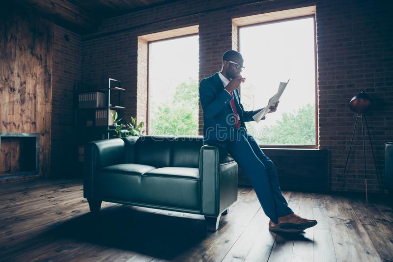 Sofa de penchement de bureau de type macho foncé de peau buvant la boisson chaude lisant le costume élégant d'usage frais de pres photo stock