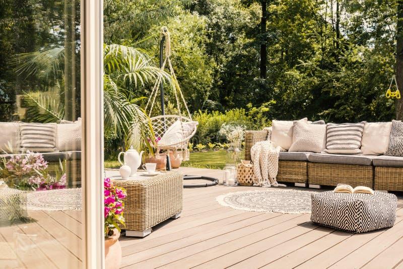Sofa de pouf et de rotin sur le patio en bois avec la chaise accrochante dans le g photo stock