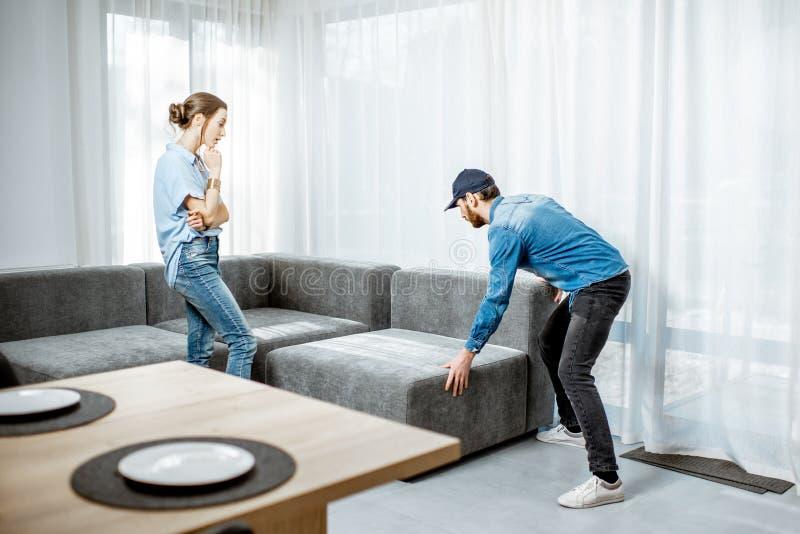 Sofa de support d'homme avec la femme dans l'appartement photographie stock libre de droits