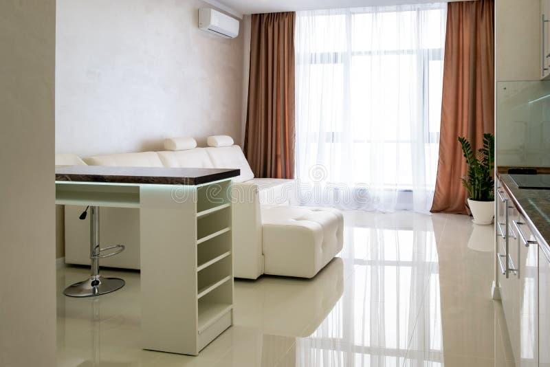 Sofa en cuir dans le salon avec de grandes fenêtres en nouvel appartement photos libres de droits