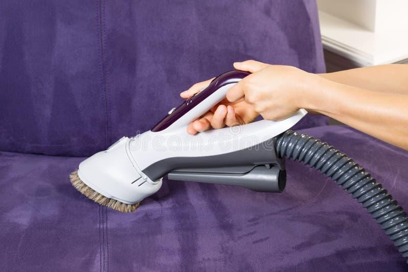 Sofa en cuir de nettoyage avec la brosse de vide images libres de droits