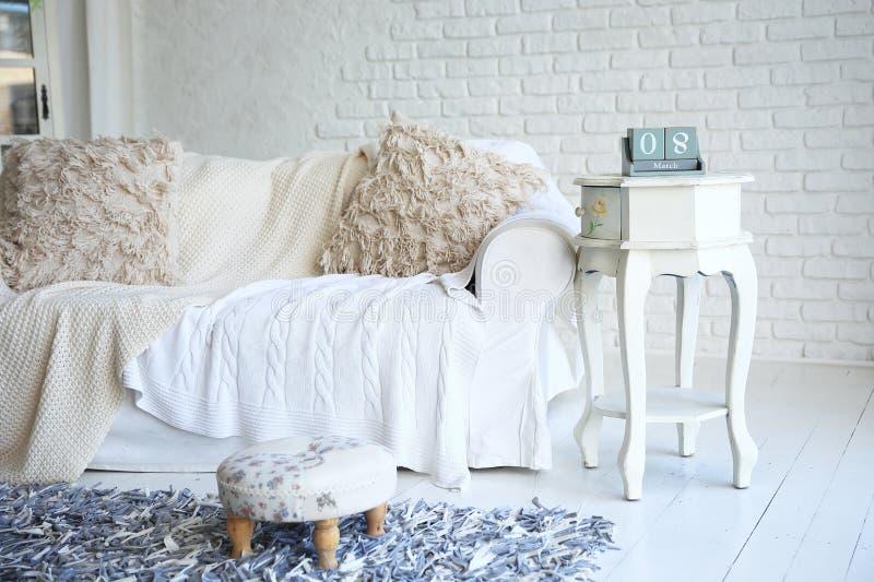 Sofa et nightstand blancs avec le calendrier de changement dans un salon élégant images libres de droits