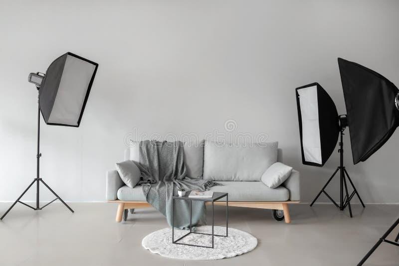 Sofa et table confortables dans le studio de photo avec l'équipement professionnel photos libres de droits