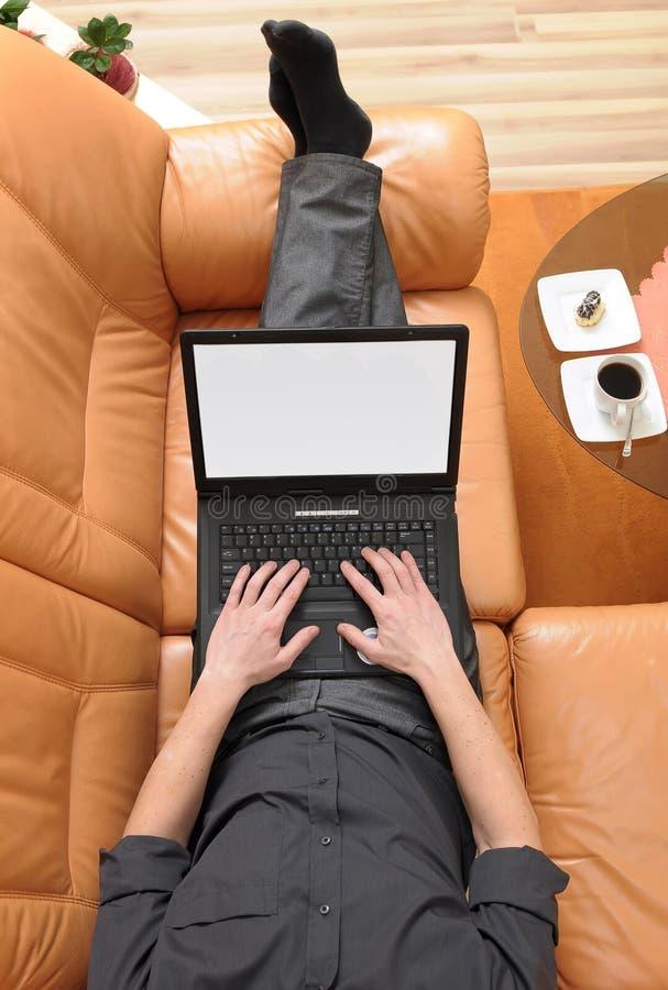 sofa för affärsmankaffebärbar dator arkivbild