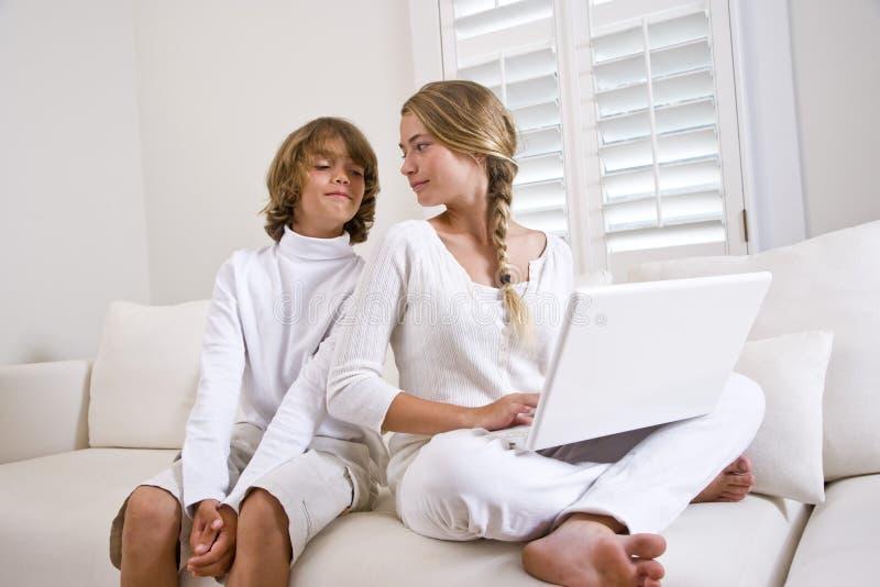 sofa för broderbärbar datorsyster genom att använda white royaltyfri fotografi