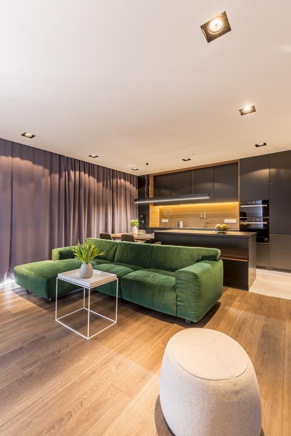 Sofa faisant le coin vert et table d'extrémité blanche avec les tulipes fraîches dans le vase dans l'intérieur moderne de salon a image libre de droits