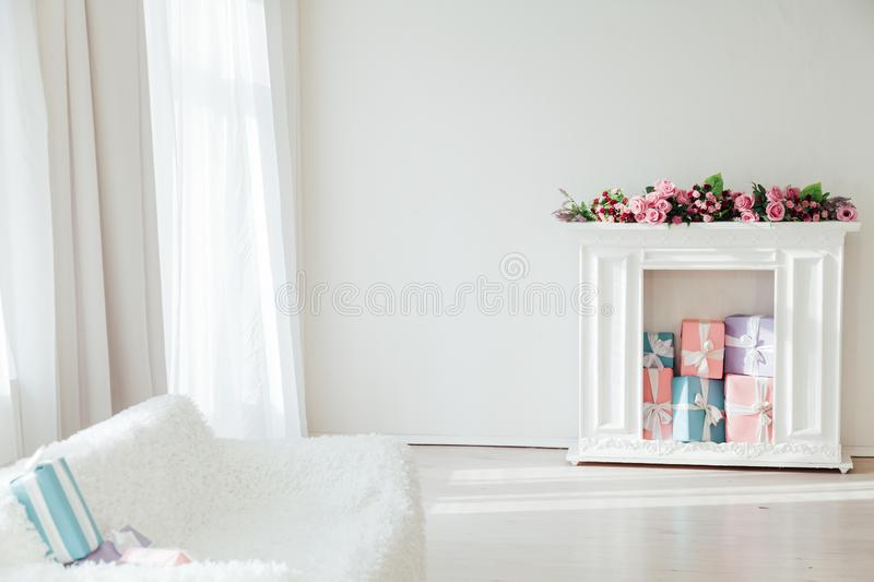 White sofa with a fireplace in the interior of a white room with windows. Sofa with a fireplace in the interior of a white room with windows stock photo