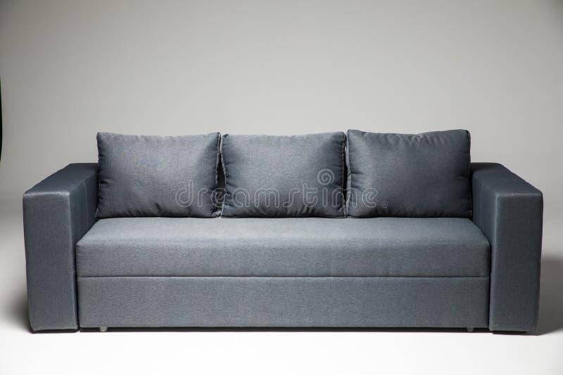 Sofa gris d'isolement sur le fond gris photo stock