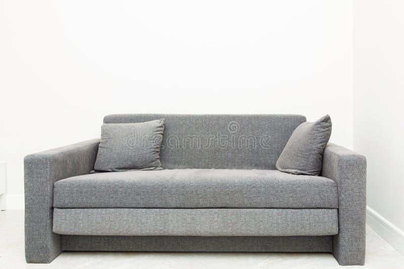 Sofa gris moderne classique avec des oreillers dans l'intérieur lumineux de l'appartement images stock