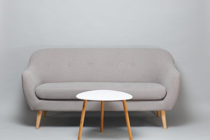 Sofa gris moderne et table basse blanche sur les jambes en bois d'isolement sur le fond gris de mur dans le studio Intérieur mini photographie stock