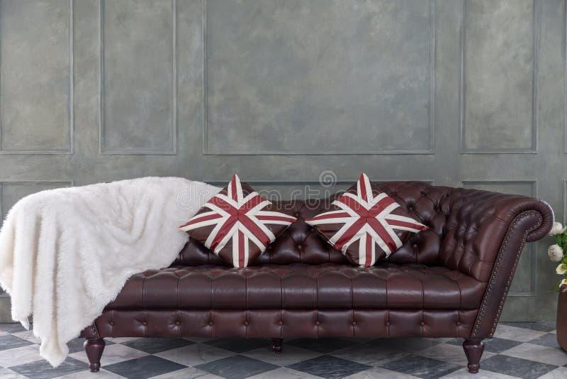 Sofa luxueux en cuir de Brown avec l'oreiller et la laine photo libre de droits