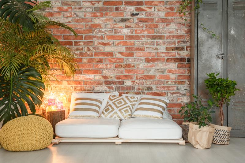 Sofa made of pallets. White sofa made of wooden pallets in cozy living room royalty free stock photography