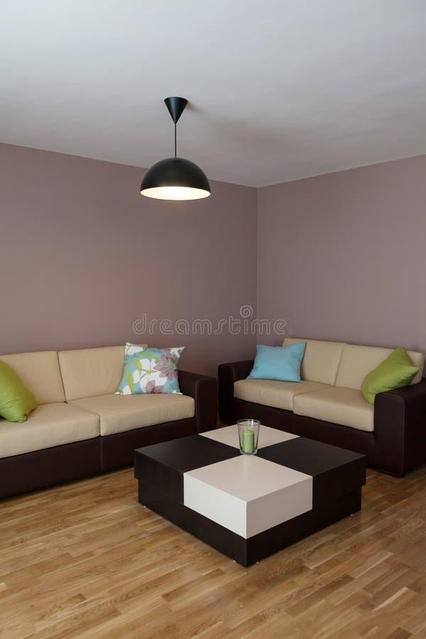 Sofa mit drei Kissen und Tabelle stockfotografie