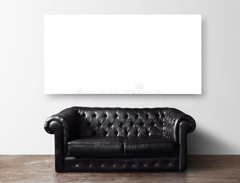 Sofa and poster. Black leather sofa in room and blank poster on wall stock photo