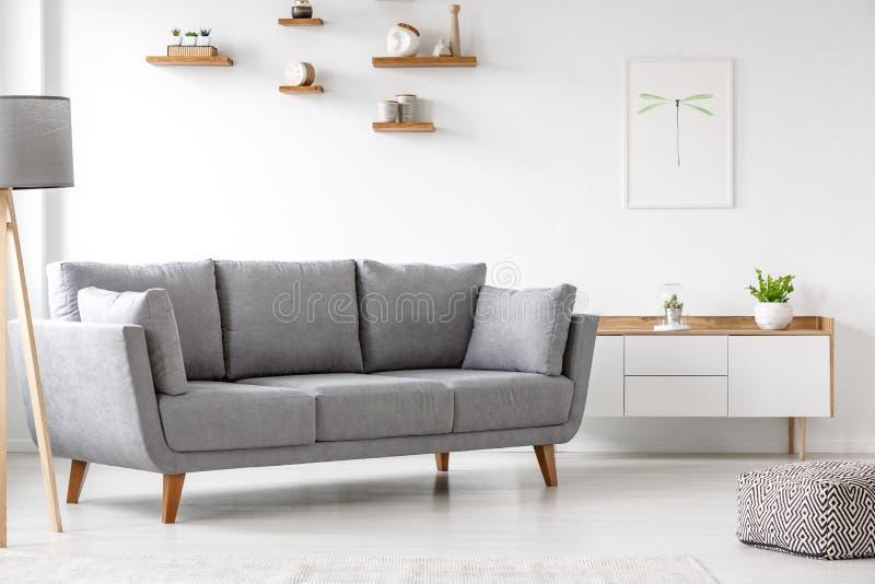 Sofa simple et gris se tenant à côté d'un placard blanc dans le RO vivant photos stock