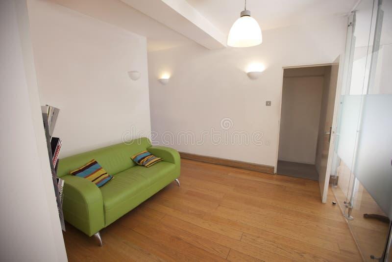Sofa vert dans le bureau vide photos stock